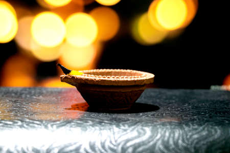 Happy Diwali. Clay diya candle illuminated in Dipavali, Hindu festival of lights. Traditional oil lamp on dark background