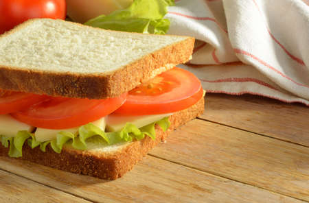 Sandwich with cheese and tomato on wooden table
