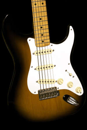 strat: A sunburst colored electric guitar emerges from a black background Stock Photo