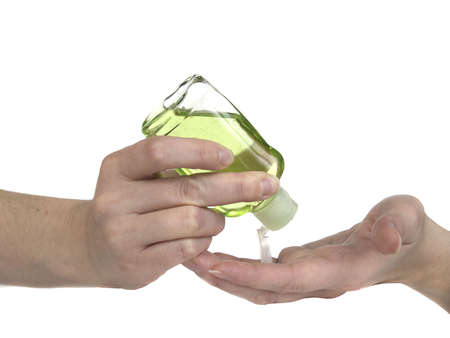 dispense: Woman squeezing green hand sanitizer lotion onto her hands.