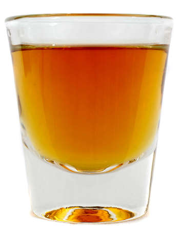 full shot: Beautiful side on shot of a shot glass full of brown whiskey or brandy