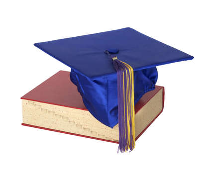 A colorful graduation cap resting on top of a text book. photo
