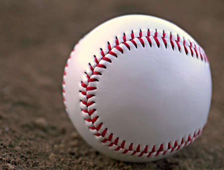 Closeup of a Baseball Sitting in Infield Dirt photo