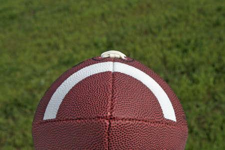 quarterback: Football sitting on a green grass background Stock Photo