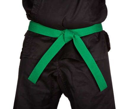 dojo: Karate green belt tied around marital artists torso wearing black dojo GI Stock Photo