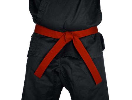 dojo: Karate red belt tied around marital artists torso wearing black dojo GI Stock Photo