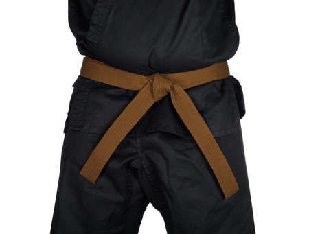 dojo: Karate brown belt tied around marital artists torso wearing black dojo GI