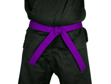 black belt: Karate purple belt tied around marital artists torso wearing black dojo GI