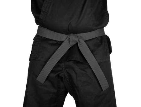 dojo: Karate grey belt tied around marital artists torso wearing black dojo GI