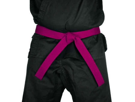 dojo: Karate pink belt tied around marital artists torso wearing black dojo GI