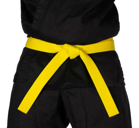 expertise: Karate yellow belt tied around marital artists torso wearing black dojo GI Stock Photo
