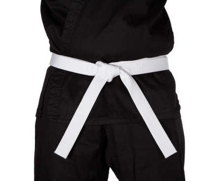 gi: Karate white belt tied around marital artists torso wearing black dojo GI Stock Photo