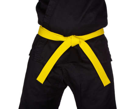 dojo: Karate yellow belt tied around marital artists torso wearing black dojo GIs. Stock Photo