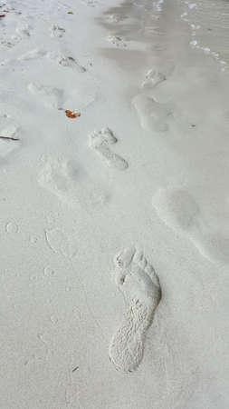 Real footprints on sand beach