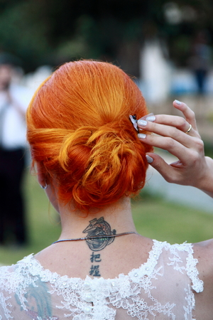 with a neck tattoo redhead bride at wedding