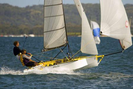 skiff: Cherub class sailing dinghy planes under spinnacker, with crew enjoying a trapeze ride