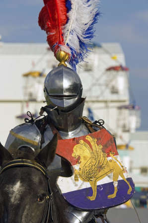 Fully armoured and shielded knight on horseback during medieval reenactment display