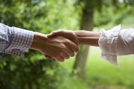 friendly people: a relaxed handshake, a businessman in partnership with an artist.