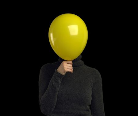 metamorphosis: A yellow balloon over a persons face Stock Photo