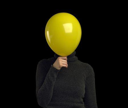 Een gele ballon over een gezicht personen