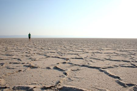 salt flat: young man walking in the desert