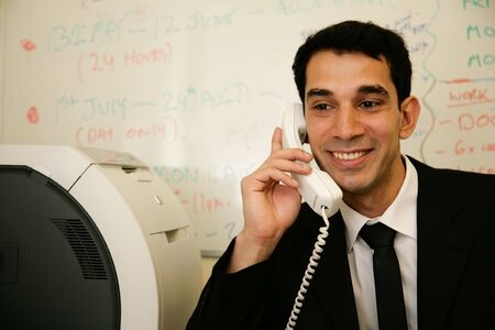 a worker answers the telephone in his office photo