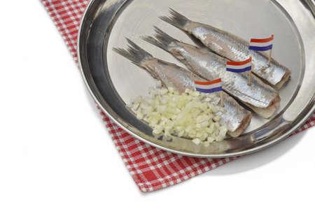 Haringfilets, Silver Fish on Silver Plate met gehakte uien en Nederlandse vlaggen Stockfoto