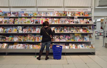 Een vrouw leest een aantal glossies in een hypermarkt in België