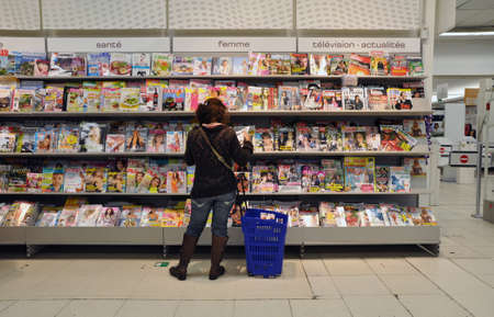 A woman is reading some glossies in a hypermarket in Belgium Editoriali