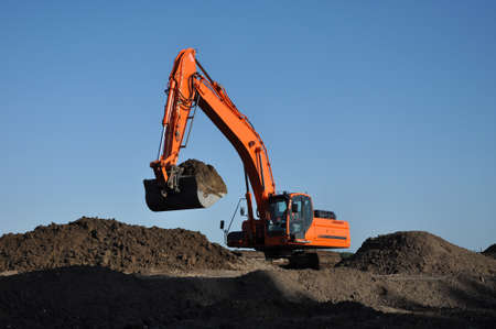 Orange excavator at work in open sand mine and a blue sky Standard-Bild