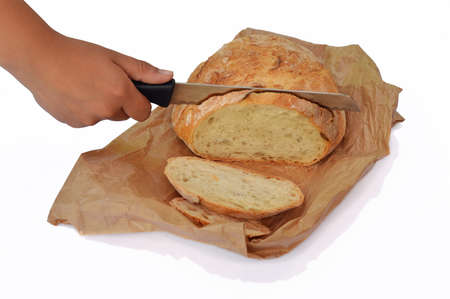 Bread cut by knife on paperbag, isolated on white photo