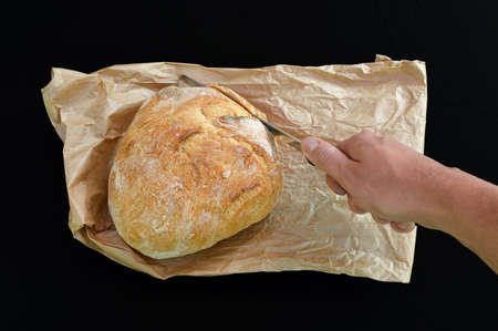 Hand with knife and bread on paperbag isolated on black photo