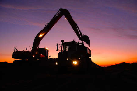 Silhouette of a mechanical digger loading an articulated dump truck or dumper