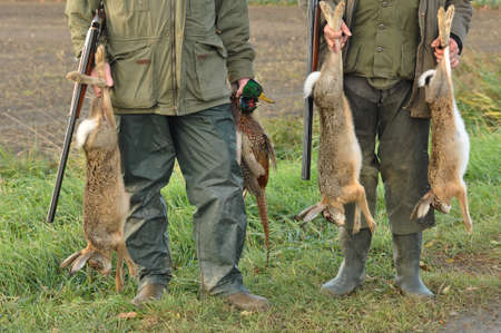 poaching: Hunters with Catch: Hare, Duck and Pheasant in hand Editorial