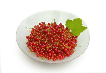 A glass bowl with red currant with a leaf isolated on white photo