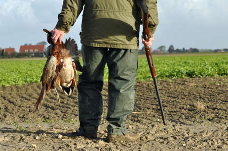 Hunter with rifle and prey at hunt  Editoriali