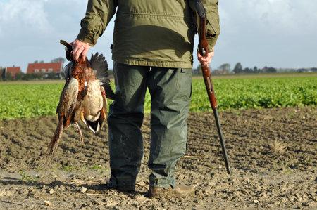 Hunter avec le fusil et proie à la chasse