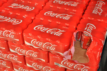 A Pallet with 15-packs of shrink wrapped  Coke cans, one is opened