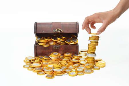 Stapel chocolade snoep euromunten, een schatkist op de achtergrond Stockfoto