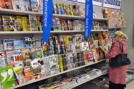 carrefour market: Belgium - July 29, 2010 : Woman is reading some glossies in a hypermarket in Belgium