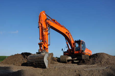 sand quarry: Orange excavator at work in open sand mine and a blue sky Stock Photo
