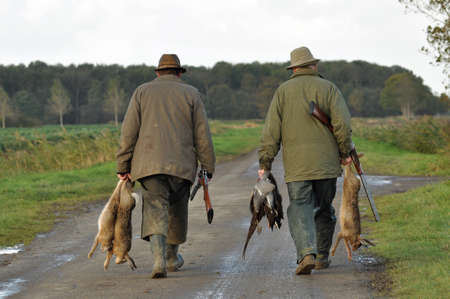 hunters: Hunters with rifles and prey: Hare, Duck and Pheasant in hand finished their hunt