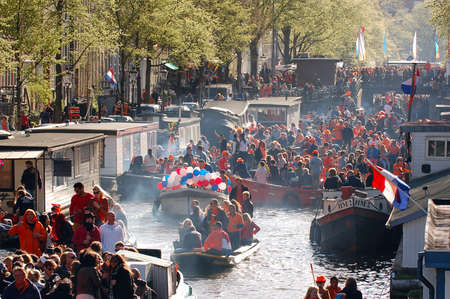 cruiseboat: Amsterdam, The Netherlands - April 30, 2013 : Celebration of queensday on a Amsterdam canal with houseboats Editorial