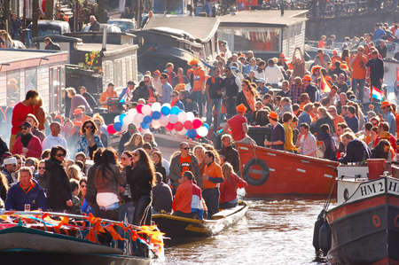 Amsterdam - April 30: Celebration of queensday on a Amsterdam canal with houseboats on April 30, 2013 in Amsterdam, The Netherlands