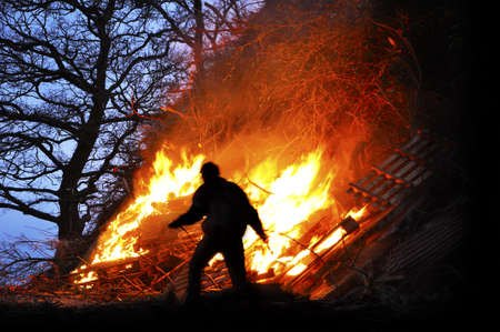 campfires: Bonfire - Silhouette of a man in front of a big Easter fire Stock Photo