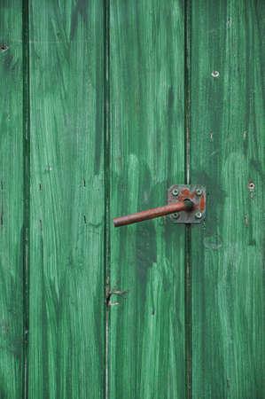 Hand painted green wooden door with metal handle photo
