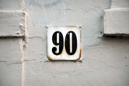 House Number Ninety sign on white painted plasterwork wall Stock Photo