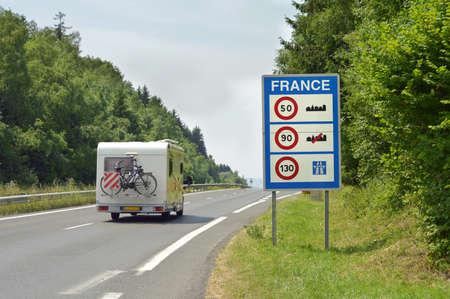Camper passeren het teken van Snelheidsbeperkingen aan de Franse grens Stockfoto