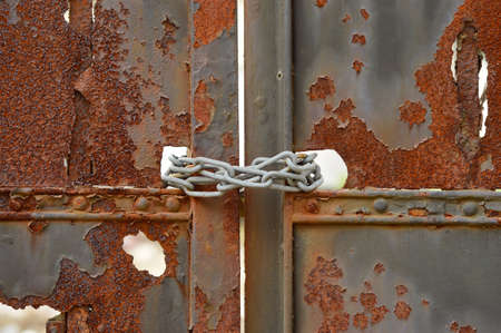 Chained - Rusty metal gate closed with chain photo