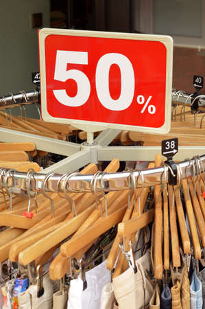 Sale in a clothing store - 50  discount sign at a clothes rack with Fashion outlet Zdjęcie Seryjne